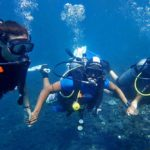 Dive instructor Nyoman helping out beginner divers in Tulamben Bali Indonesia