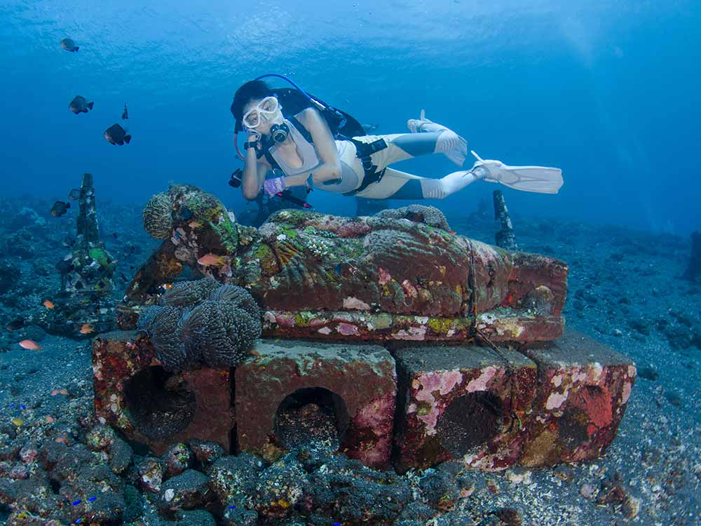 Scuba Diver posing with statue at Coral Garden in Tulamben, Bali